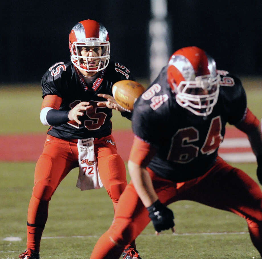 New Canaan quarterback Nick Cascione (# 15) takes the snap from teammate and center, Ryan McKenna (# 64) during the Class L high school football quarterfinals, New Canaan High School vs. Farmington High School, at New Canaan, Tuesday night, Dec. 3, 2013. Photo: Bob Luckey / Greenwich Time