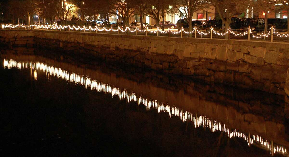 A block away from Main Street, strands of white lights strung along the railing in Parker Harding Plaza reflect brightly off the Saugatuck River.
