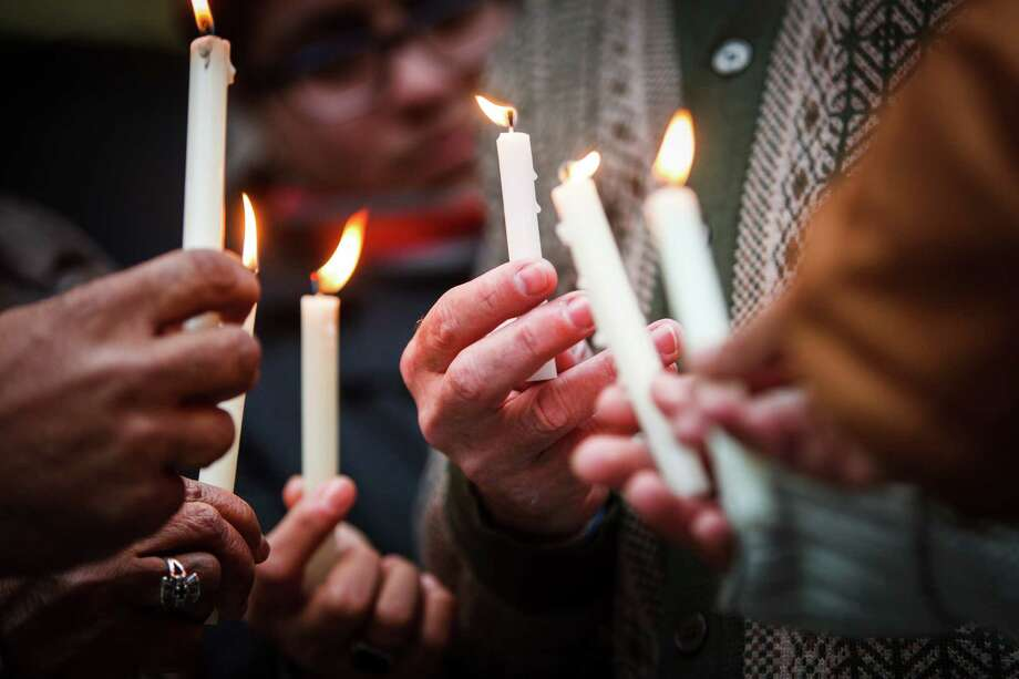 Johan Zaayman, center, and others hold candles as they take part in a prayer vigil in honor of Nelson Mandela outside the Bob Casey Federal Courthouse on Friday. Photo: Michael Paulsen, Houston Chronicle / © 2013 Houston Chronicle