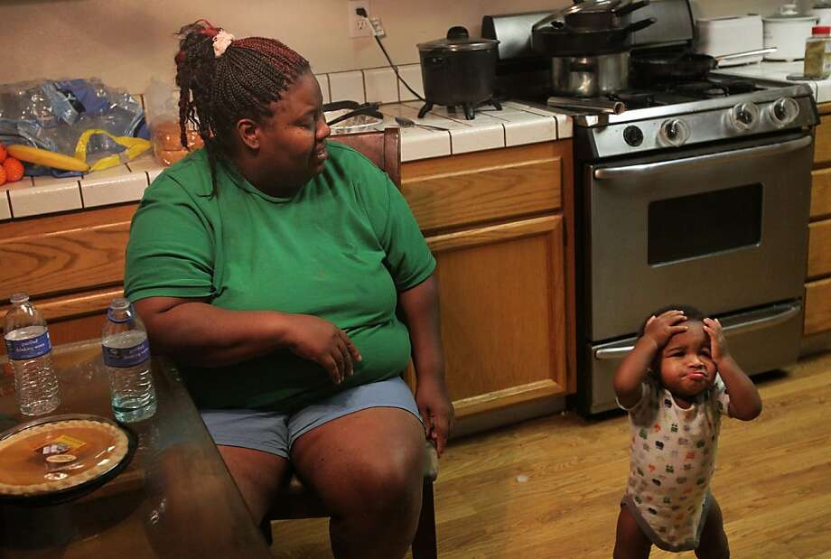 Yvette Peters watches nephew and foster baby Angel Nash, 11 months, toddle playfully around the kitchen. Photo: Leah Millis, The Chronicle