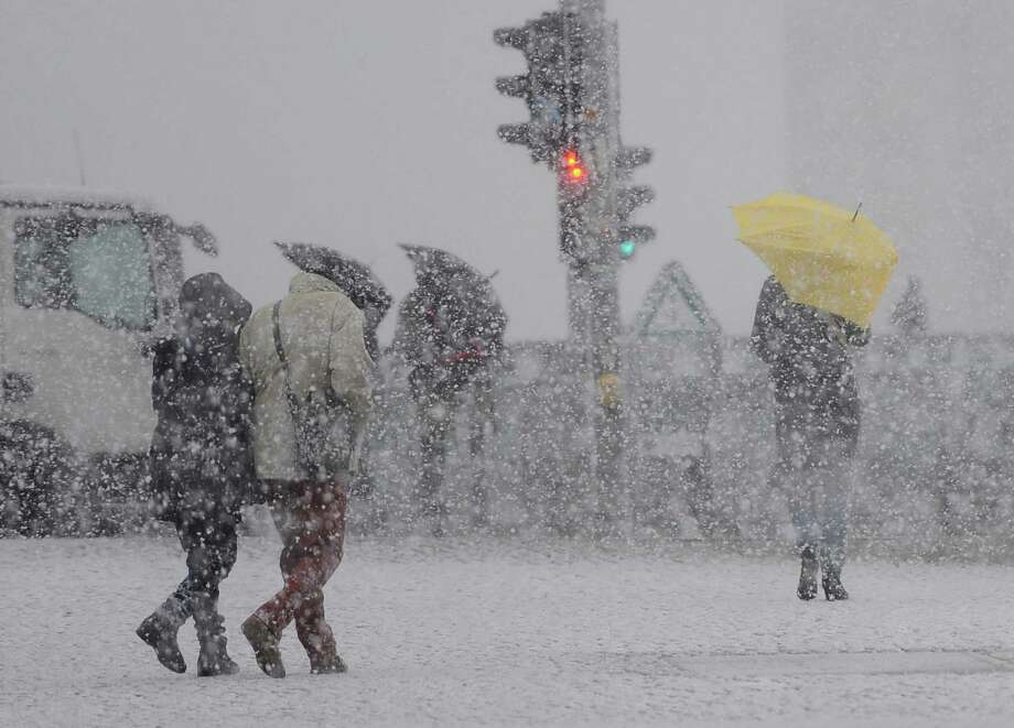 Pedestrians make their way during heavy snowfalls  near Berlin's central station Friday Dec. 6, 2013.  Weather forecasts predict ongoing stormy weather with low temperatures in Germany. (AP Photo/dpa, Britta Pedersen) Photo: Britta Pedersen, Associated Press / dpa