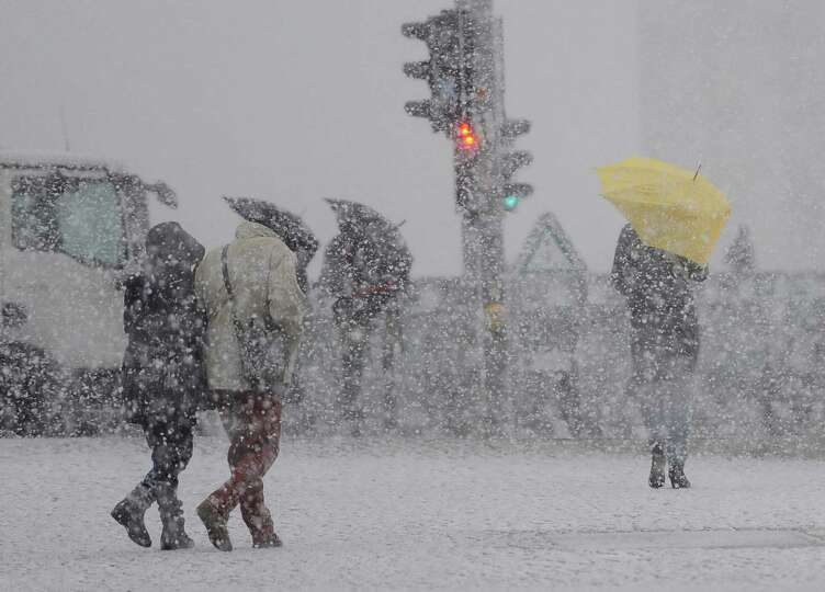 Pedestrians make their way during heavy snowfalls  near Berlin's central station Friday Dec. 6, 2013