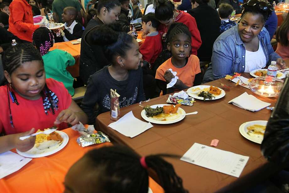 Cheryl Fields (right) chats with her daughter, Aneiyah Fields, 9 (left), her friend Maleina Benard, 9 (center left), and Myjah Williams, 7, during an annual Thanksgiving lunch at John Muir Elementary School in San Francisco. Photo: Leah Millis, The Chronicle