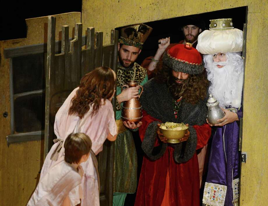 """Three kings dressed in green, red and purple, Stephen Wynn as Balthazar, Steve Valenzuela as Melchior, and Erick Sanchez as Kaspar, with Page, behind, played by Ryan Reynolds, enter the home of Amahl and his mother, played by Chase Harper and Diana Rock, in the opera """"Amahl and the Night Visitors"""" in Ives Auditorium on the campus of Western Connecticut State University in Danbury, Conn. on Friday, Dec. 6, 2013.  The production is set near Bethlehem, featuring three kings on their way to give gifts to a wonderous child, encountering a young boy named Amahl, notorious for lying, and his mother along their journey.  The kings stay at their house and teach Amahl selflessness, which miraculously heals his disabled leg.  The opera is directed by Dr. Margaret Astrup and features Chase Harper as Amahl and Diana Rock as his mother.  The performance will be held again Saturday at 7:30 p.m.  Tickets are $12 for adults, $8 for senior citizens, non-West Conn. students, and children under 12.  West Conn. students are admitted for free with a valid ID. Photo: Tyler Sizemore / The News-Times"""