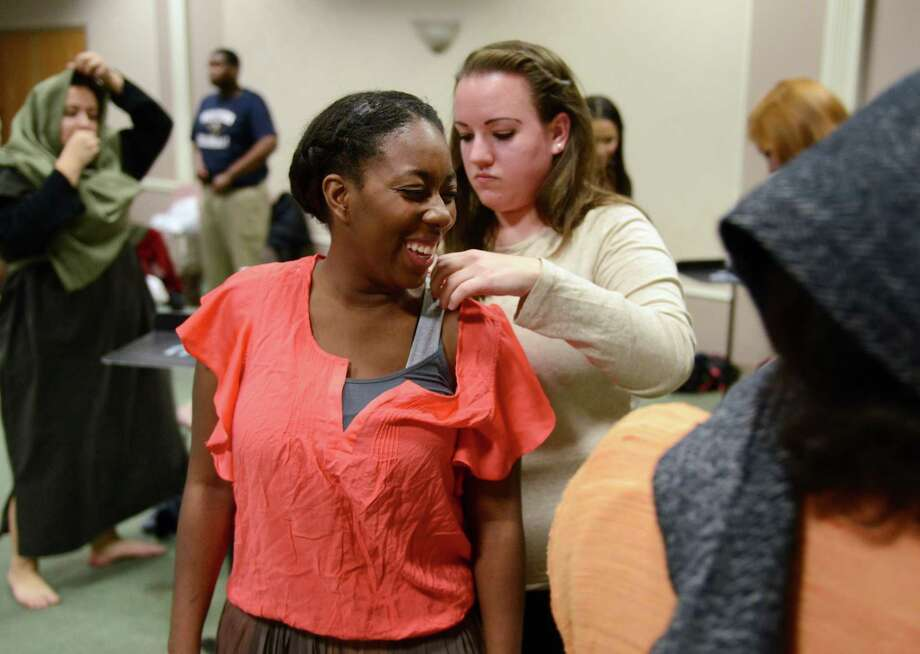 """Dancer Delecia Woods gets dressed with help from Maureen Holland, playing a shepherd, before their performance in the opera """"Amahl and the Night Visitors"""" in Ives Auditorium on the campus of Western Connecticut State University in Danbury, Conn. on Friday, Dec. 6, 2013.  The production is set near Bethlehem, featuring three kings on their way to give gifts to a wonderous child, encountering a young boy named Amahl, notorious for lying, and his mother along their journey.  The kings stay at their house and teach Amahl selflessness, which miraculously heals his disabled leg.  The opera is directed by Dr. Margaret Astrup and features Chase Harper as Amahl and Diana Rock as his mother.  The performance will be held again Saturday at 7:30 p.m.  Tickets are $12 for adults, $8 for senior citizens, non-West Conn. students, and children under 12.  West Conn. students are admitted for free with a valid ID. Photo: Tyler Sizemore / The News-Times"""