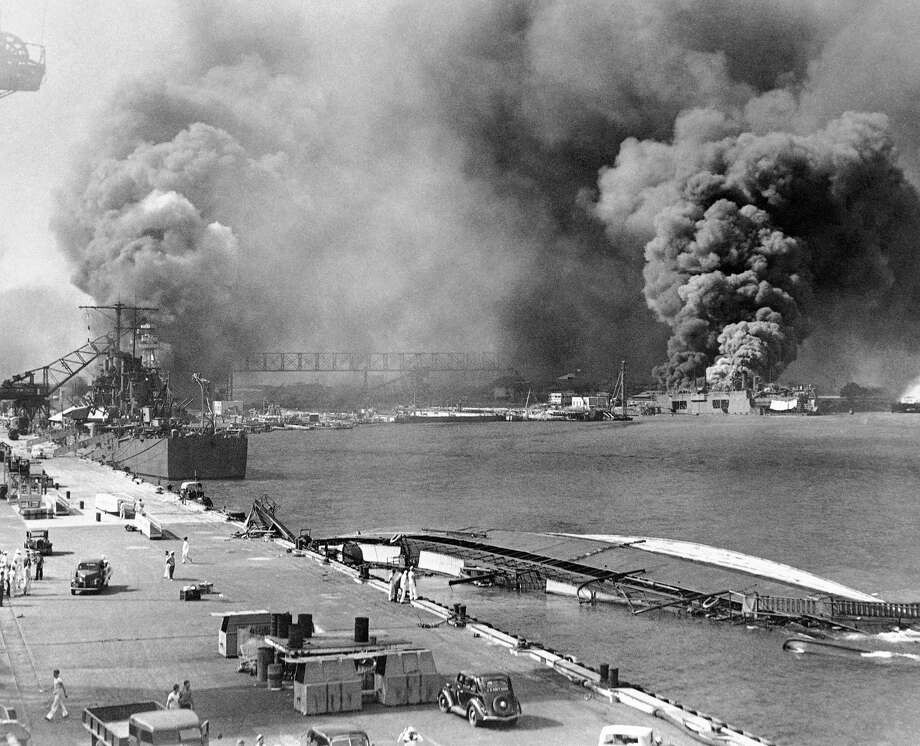 In this image provided by the U.S. Navy, a pall of smoke filled the sky over Pearl Harbor, Hawaii on Dec. 7, 1941, after the Japanese attacked. In the foreground is the capsized minelayer, the USS Oglala, and to the left appears the moored USS Helena, 10,000-ton cruiser, struck by a bomb. Beyond the superstructure of the USS Pennsylvania, and at the right is the USS Maryland, burning. At right center the destroyer Shaw is ablaze in drydock. Photo: Anonymous, AP Photo / AP1941