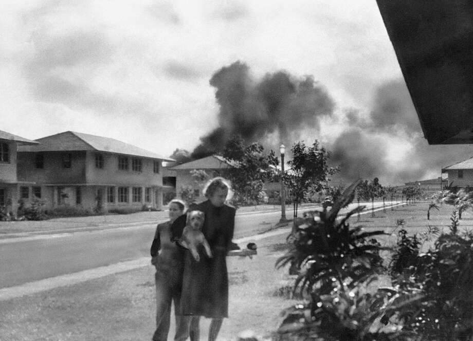 """An unidentified officers' wife, investigating explosion and seeing smoke pall in distance at 8:15 am Dec. 7, 1941, heard neighbor Mary Naiden, then an army hostess, exclaim �There are red circles on those planes overhead. They are Japanese!""""  A boy and a woman carrying a dog flee toward quarters. Photo: Mary Naiden, AP Photo / AP1941"""