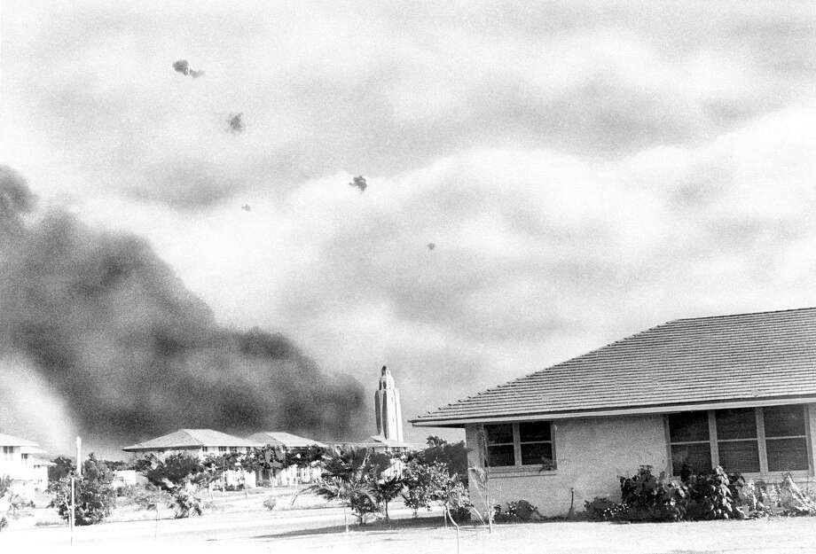 A Japanese plane, braving American anti-aircraft fire, proceeds toward �battleship row,� Pearl Harbor, after other bombers had hit USS. Arizona, from which smoke billows, Dec. 7, 1941. Photo: AP Photo / AP1941