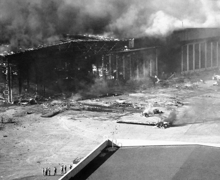 In this photo provided by the U.S. Navy, giant hangar at the U.S. Naval Air Station at Pearl Harbor is fringed in flames caused by Japanese bombs which wrecked the installation, Dec. 7, 1941. Planes on aprons and runways were burned and shattered. Wreckage of some may be seen in foreground. Photo: Anonymous, AP Photo / AP1941