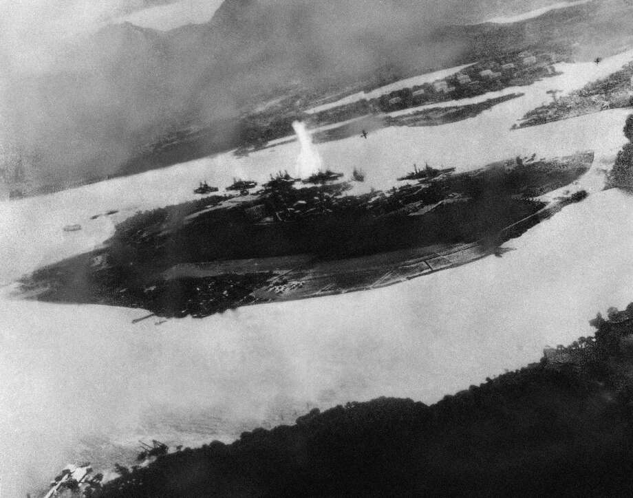 Believed to be the first bomb dropped on Pearl Harbor, Hawaii in the sneak-attack on Dec. 7, 1941, this picture was found torn to pieces at Yokusuka Base by photographer's mate 2/C Martin J. Shemanski of Plymouth, Pa. One Japanese plane is shown pulling out of a dive near bomb eruption (center) and another the air at upper right. Photo: AP Photo / 1941 AP