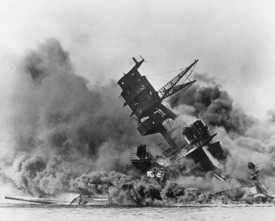 "The battleship USS Arizona belches smoke as it topples over into the sea during a Japanese surprise attack on Pearl Harbor, Hawaii,  Dec. 7, 1941. The ship sank with more than 80  percent of its 1,500-man crew, including Rear Admiral Isaac C. Kidd . The attack, which left 2,343 Americans dead and 916 missing, broke the backbone of the U.S. Pacific Fleet and forced  America out of a policy of isolationism. President Franklin D. Roosevelt announced that it was ""a date which will live in infamy"" and Congress declared war on Japan the morning after. This was the  first attack on American territory since 1812. Photo: Anonymous, AP Photo / 1941 AP"