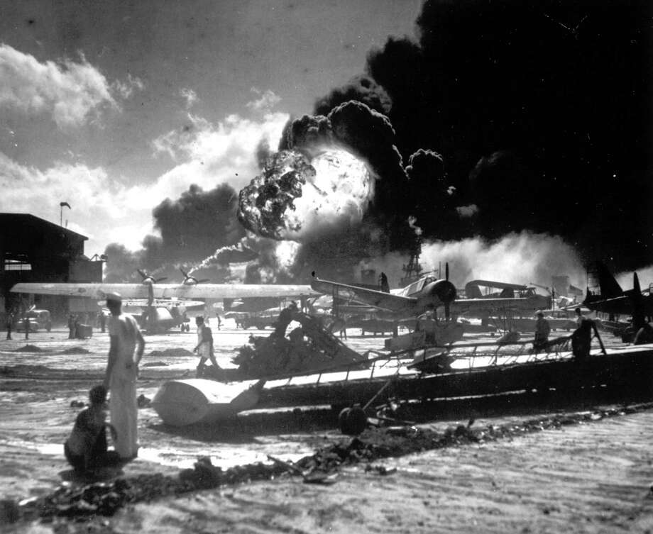 Sailors stand among wrecked airplanes at Ford Island Naval Air Station as they watch the explosion of the USS Shaw in the background, during the Japanese surprise attack on Pearl Harbor, Hawaii, on December 7, 1941. Photo: AP Photo / AP1941