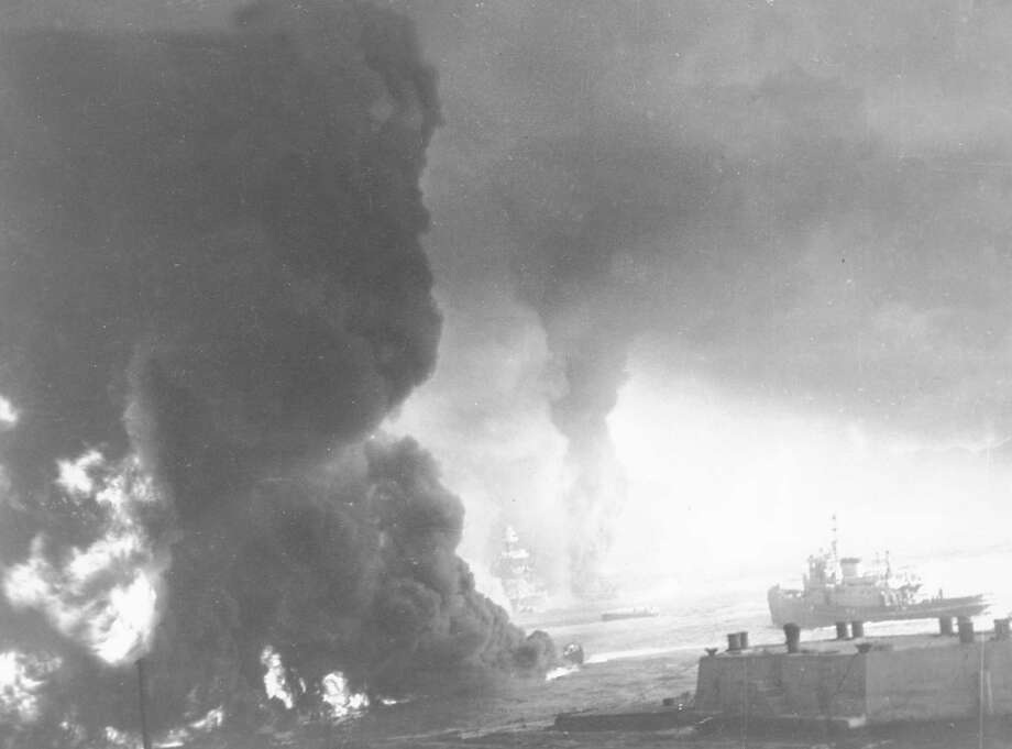 Heavy black smoke billows as oil fuel burns from shattered tanks on ships that were hit during the Japanese attack on Pearl Harbor, Hawaii on Dec. 7, 1941 during World War II.  Visible through the murk is the U.S. battleship Maryland, center, and the hulk of the capsized USS Oklahoma to the right of it. Photo: AP Photo / AP1941