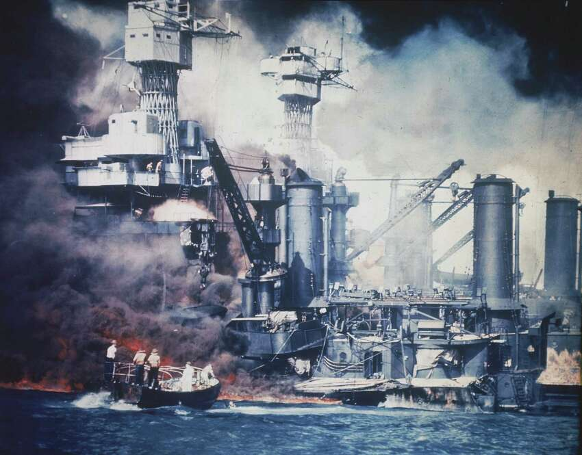 A small boat rescues a USS West Virginia crew member from the water after the Japanese bombing of Pearl Harbor, Hawaii on Dec. 7, 1941 during World War II. Two men can be seen on the superstructure, upper center. The mast of the USS Tennessee is beyond the burning West Virginia.