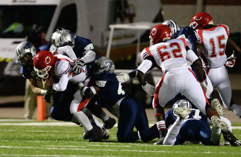 """Carthage quarterback Blake Bogenschutz, No. 4, is brought down by a group of West Orange-Stark defenders during Friday night's game. West Orange-Stark High School played against Carthage High School at the Carroll A. """"Butch"""" Thomas Stadium on Friday night. Photo taken Jake Daniels/@JakeD_in_SETX Photo: Jake Daniels / ©2013 The Beaumont Enterprise/Jake Daniels"""