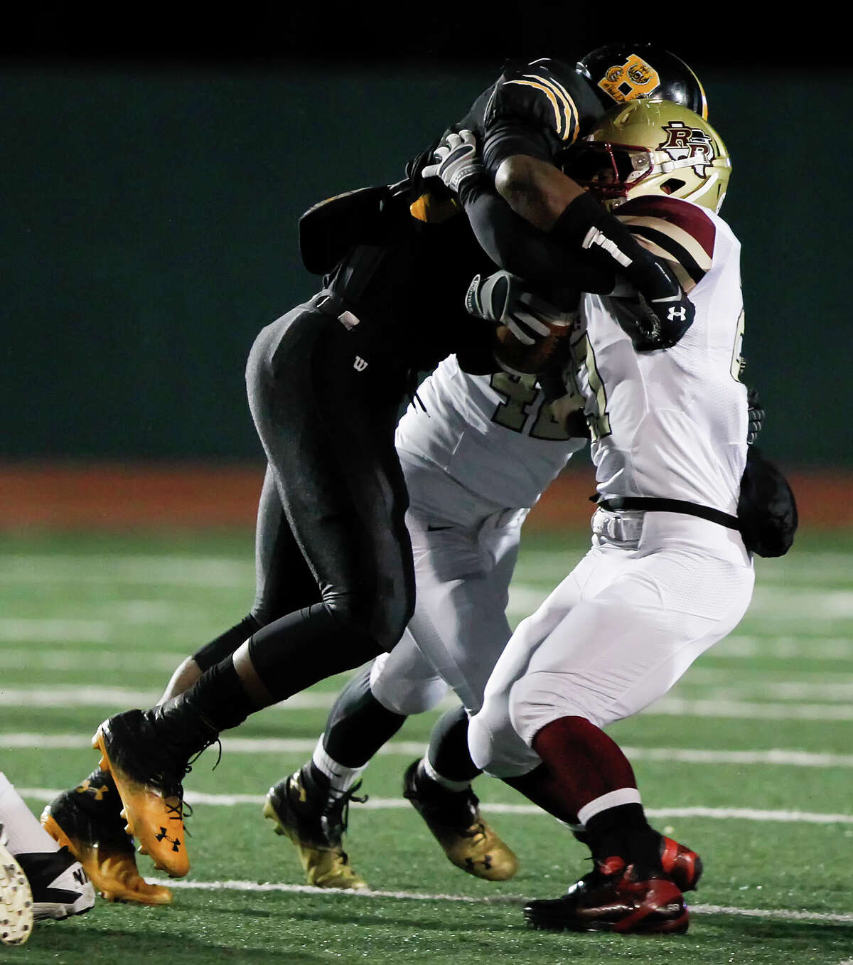 Brennan's Derick Roberson (left) stops Leander Rouse's Kevin Cole during the first half of their Class 4A Division I state quarterfinal game at Comalander Stadium on Friday, Dec. 6, 2013. MARVIN PFEIFFER/ mpfeiffer@express-news.net