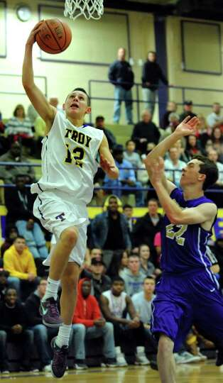 Troy's Zach Radz, left, goes to the hoop a CBA's Matt Hamel defends during their basketball game on