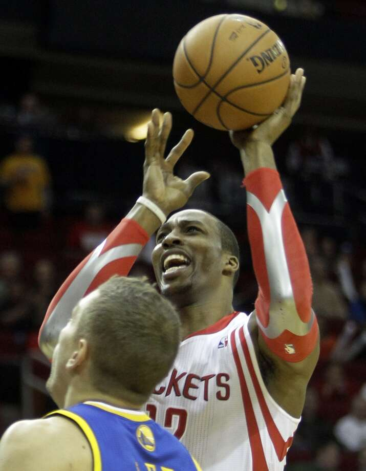 Dwight Howard shoots over David Lee. Photo: Melissa Phillip, Houston Chronicle