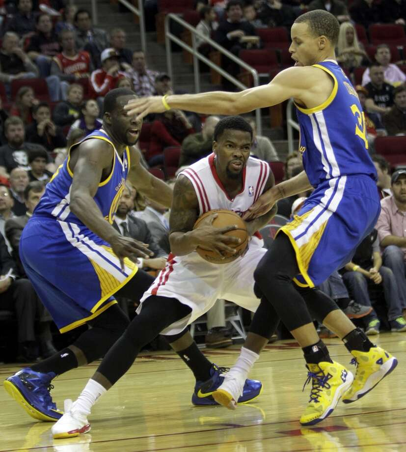 Aaron Brooks, center, works to move between Draymond Green, left, and Stephen Curry, right. Photo: Melissa Phillip, Houston Chronicle