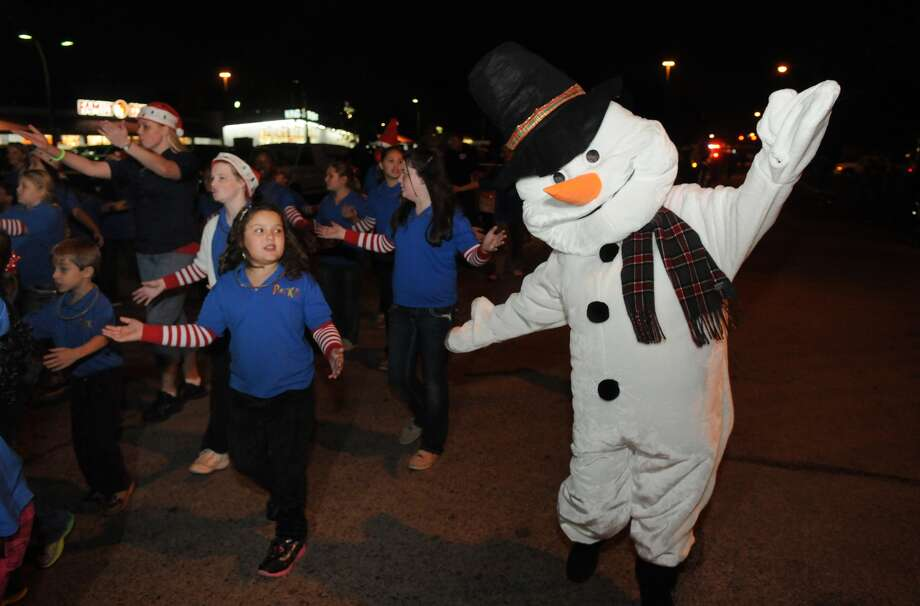 Merrell Scott, right, of Humble, dressed as Frosty the Snowman, dances with the Humble Area First Baptist Church Praise Kids during the annual Humble Christmas Parade of Lights. Photo: Jerry Baker, For The Chronicle