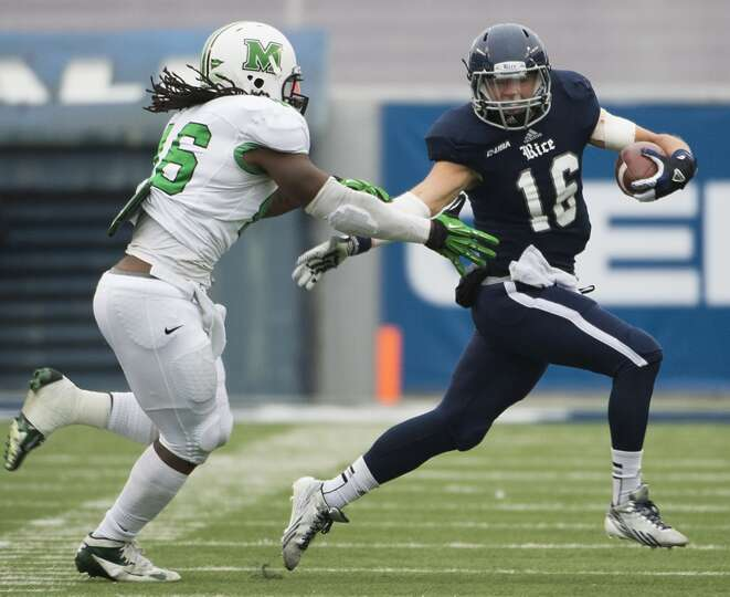 Rice quarterback Taylor McHargue tries to escape a Marshall pass rusher.