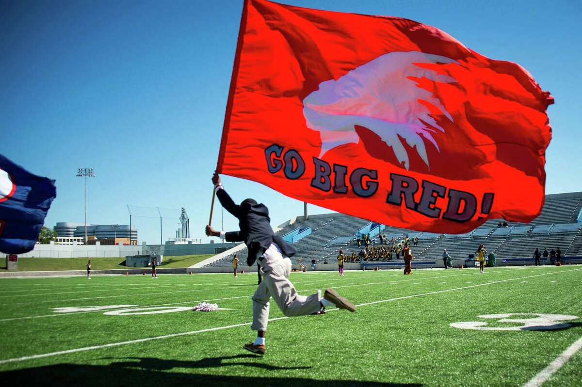 A flag bearing the Lamar High School Redskins mascot is carried across the field before a game against Sam Houston at Delmar Stadium on Saturday, Oct. 19, 2013, in Houston. ( Smiley N. Pool / Houston Chronicle )
