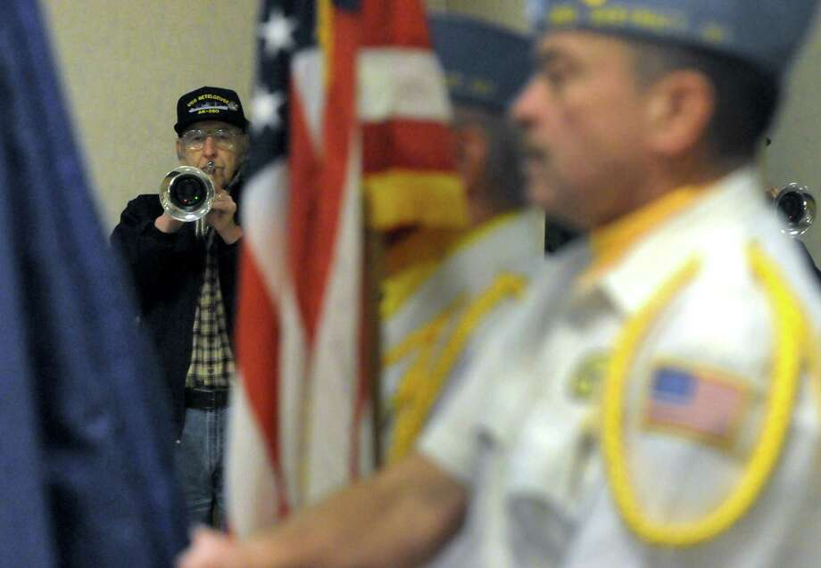 Korean War Navy veteran Richard Bender, left, plays taps during a Pearl Harbor Remembrance at the Melvin Roads American Legion Post 1231 on Saturday Dec. 7, 2013 in East Greenbush, N.Y. (Michael P. Farrell/Times Union) Photo: Michael P. Farrell / 00024776A