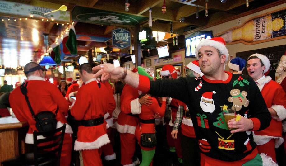 Joe Anders plays darts at Brickhouse Bar and Grill during SantaCon in Stamford, Conn., on Saturday, December 7, 2013. Photo: Lindsay Perry / Stamford Advocate