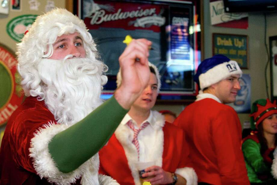 Chris Hynes plays darts at Brickhouse Bar and Grill during SantaCon in Stamford, Conn., on Saturday, December 7, 2013. Photo: Lindsay Perry / Stamford Advocate