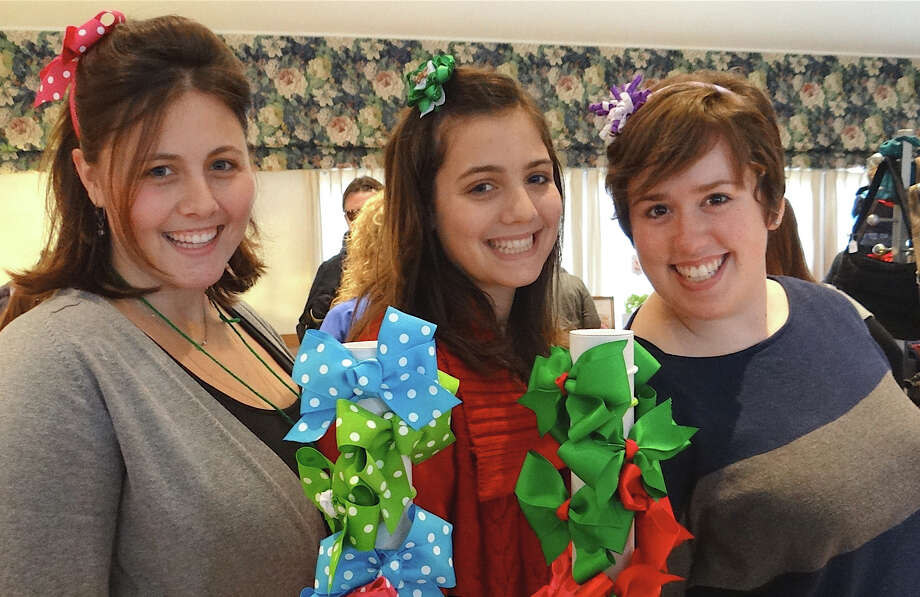 Sara Burns, Ali Burns and Meghan McNamara, of Hair Bows by Sara, sport bow accessories at the Scandinavian Club's holiday fair Saturday. Photo: Mike Lauterborn / Fairfield Citizen contributed