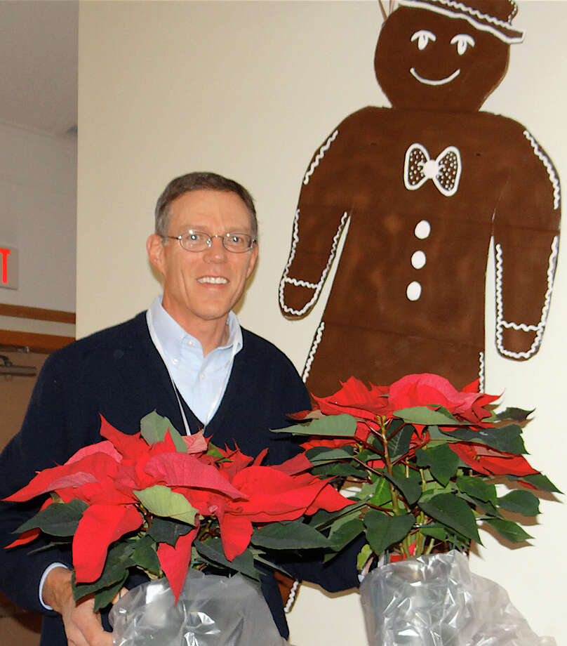 Brad Adolphson sold poinsettias at the Scandinavian Club on Saturday. Photo: Mike Lauterborn / Fairfield Citizen contributed