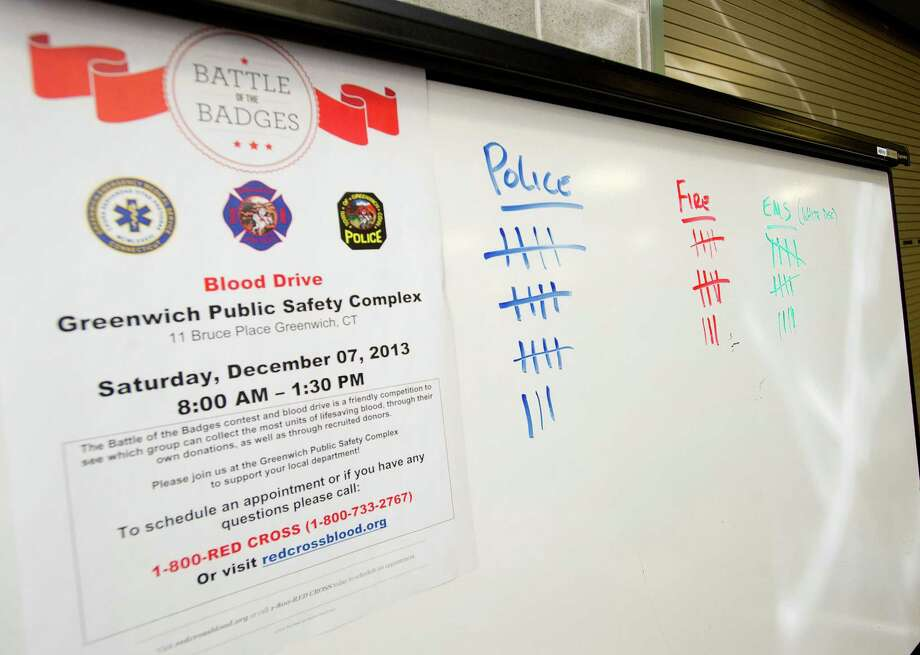 A running tally keeps track of votes for police, fire, or EMS during the Battle of the Badges contest and blood drive at the Greenwich Public Safety Complex in Greenwich, Conn., on Saturday, December 7, 2013. Photo: Lindsay Perry / Stamford Advocate
