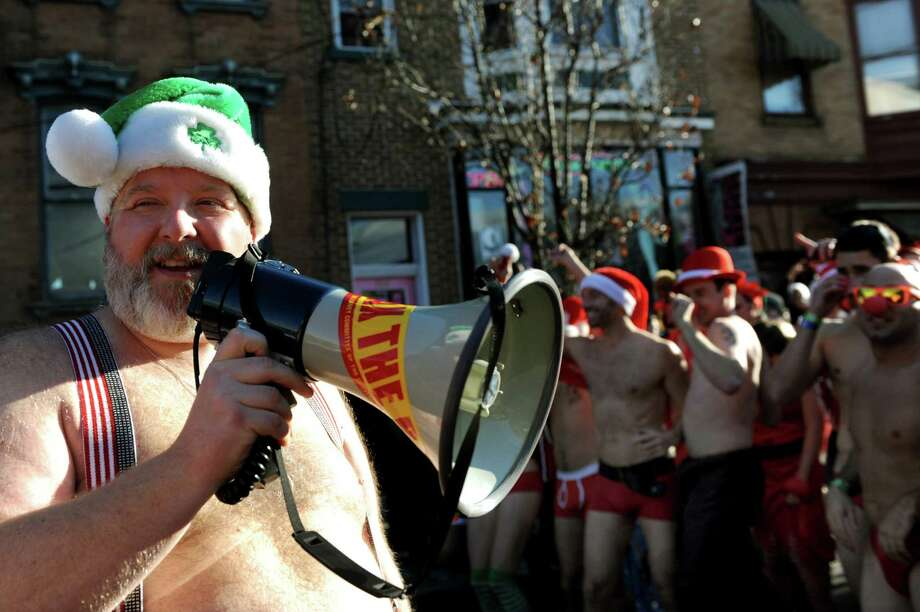 Race director Jim Larson of the Albany Society, left, announces the Santa Speedo Sprint will begin on Saturday, Dec. 7, 2013, in Albany, N.Y. The Albany Society, the ASAP Daisies and the Albany All Stars Roller Derby sponsored of the 8th annual event to benefit the Albany Damien Center and the HIV/AIDS program at Albany Medical Center. (Cindy Schultz / Times Union) Photo: Cindy Schultz / 00024885A