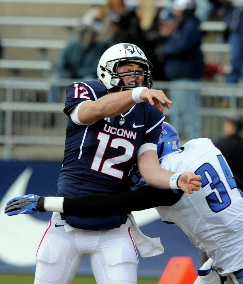 Connecticut quarterback Casey Cochran (12) is pressured by Memphis linebacker Jackson Dillon (34) during Connecticut's 45-10 victory in an NCAA college football game in East Hartford, Conn., on Saturday, Dec. 7, 2013. Photo: Fred Beckham, AP / Associated Press