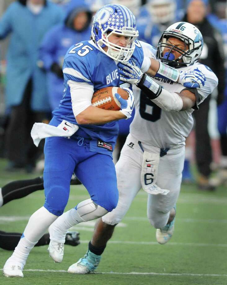 Darien running back John Reed (25) breaks free of a tackle from Middletown defender Dario Highsmith (6) to score the go-ahead touchdown in Darien's 13-7 win over Middletown in the CIAC Class L state semifinal football game at Pomperaug High School in Southbury, Conn. on Saturday, Dec. 7, 2013. Photo: Tyler Sizemore / The News-Times
