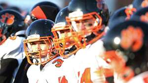 Ridgefield High School's #33 Jackson Turek, center and other teammates watch from sidelines during  Saturday afternoon's Class LL Football Semifinals against Southington High School. Southington would win 45-0.
