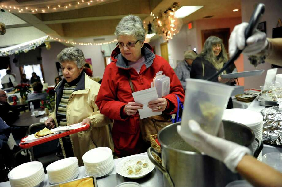 Marie VanAlstyne of Latham, left, and Pat Burns of Troy, center, order their meals during the annual Holiday Bazaar on Saturday, Dec. 7, 2013, at St. Petera€™s Armenian Church in Watervliet, N.Y. The fundraising event, which features traditional Armenian foods and baked goods, crafts and music, continues Sunday from 12 to 4 p.m. (Cindy Schultz / Times Union) Photo: Cindy Schultz / 00024874A