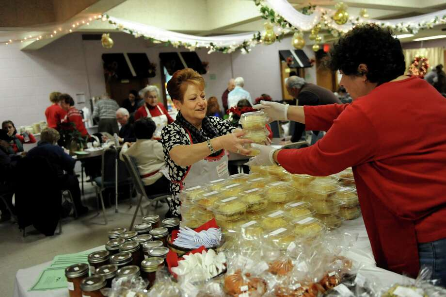 Mary Panjarjian, center, and Charlene Hrachian, right, of the Women's Guild at St. Peter's Armenian Church, replenish the baked goods table during the annual Holiday Bazaar on Saturday, Dec. 7, 2013, at St. Petera€™s Armenian Church in Watervliet, N.Y. The fundraising event, which features traditional Armenian foods and baked goods, crafts and music, continues Sunday from 12 to 4 p.m. (Cindy Schultz / Times Union) Photo: Cindy Schultz / 00024874A