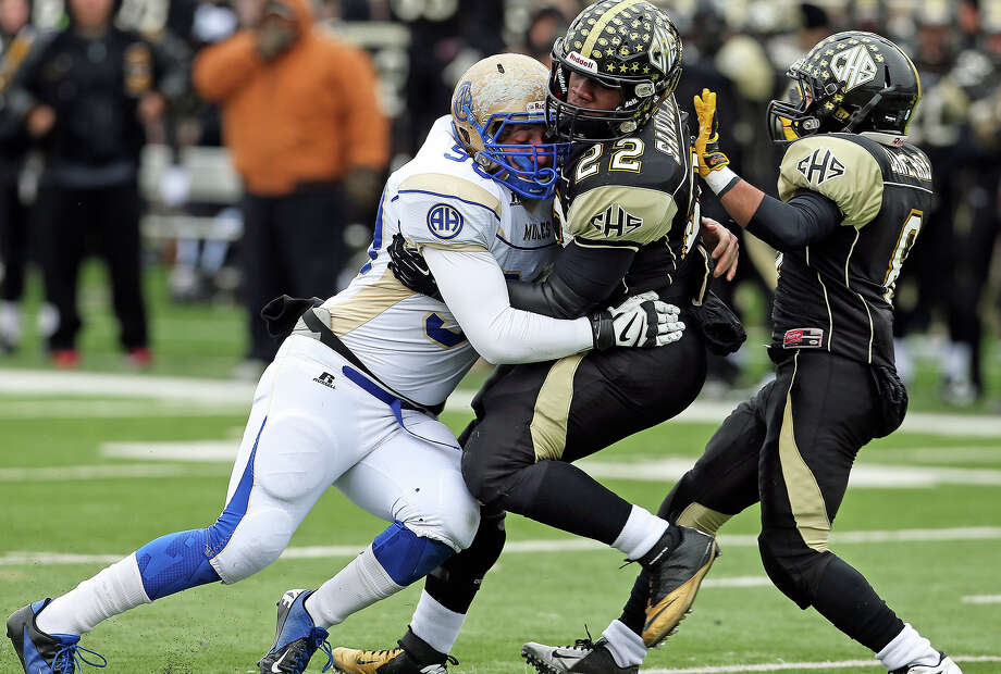 Mule defensive lineman Stone Tarver drives Sandcrab running back Cory Williams back after stopping him at the line as Alamo Heights plays Calhoun at Bobcat Stadium in the 4A quarterfinals on December 7, 2013. Photo: Tom Reel, San Antonio Express-News
