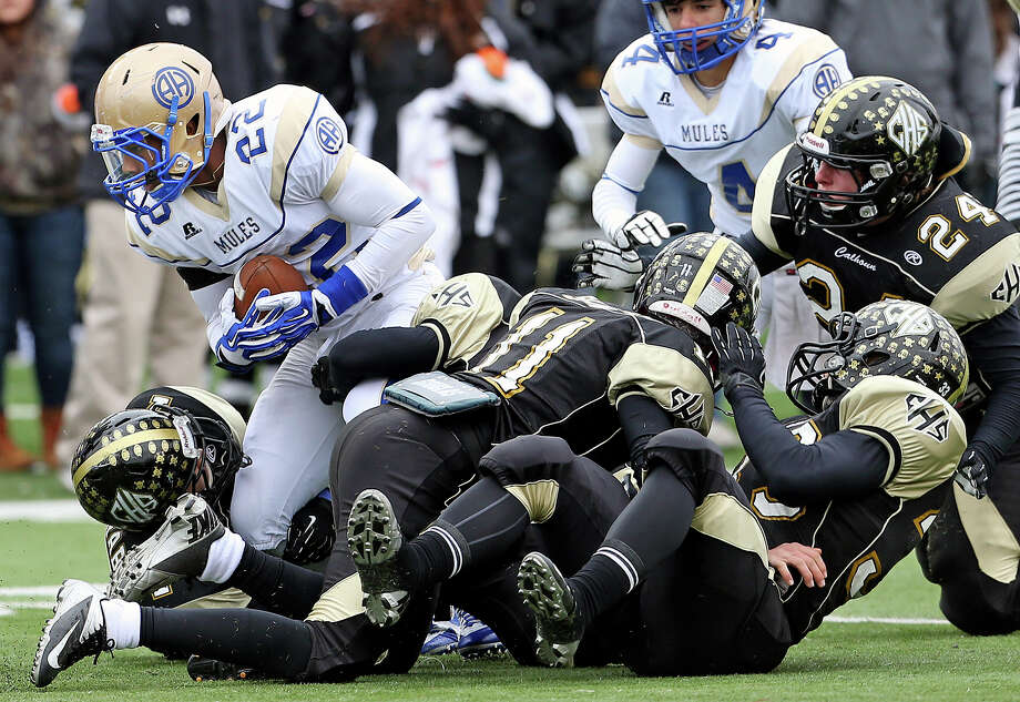 Byron Proctor gets through a pile of tacklers for the Mules in the first half as Alamo Heights plays Calhoun at Bobcat Stadium in the 4A quarterfinals on December 7, 2013. Photo: Tom Reel, San Antonio Express-News