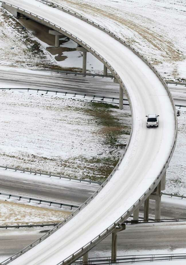 A lone vehicle is seen navigating icy road conditions on the fly over from IH-35W North to IH-35E South bound, Saturday, Dec. 7, 2013, in Denton, Texas.  Icy sections of Interstate 35 north of Dallas were closed for hours at a time over the last day as tractor-trailers had trouble climbing hills, wrecks occurred and vehicles stalled, authorities said.  Photo: Tony Gutierrez, Associated Press / AP