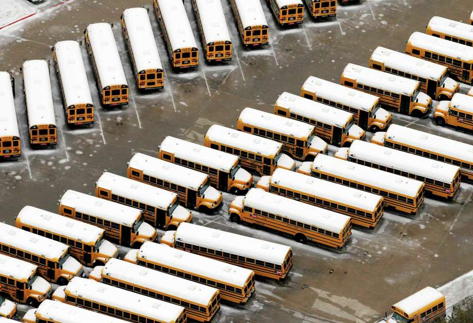 Dallas County School buses sit with ice on their roofs in a frozen over lot in North Dallas, Saturday, Dec. 7, 2013. Icy, treacherous sections of Interstate 35 north of Dallas were closed for hours at a time over the last day as tractor-trailers had trouble climbing hills, wrecks occurred and vehicles stalled, authorities said. Photo: Tony Gutierrez, Associated Press / AP