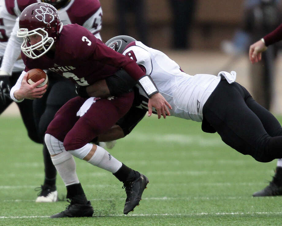 Cy-Fair quarterback Clayton Kopecky, left, is brought down by Pearland's Justin Phillips during the second half of a high school football playoff game, Saturday, December 7, 2013, at Mercer Stadium in Sugar Land. Photo: Eric Christian Smith, For The Chronicle