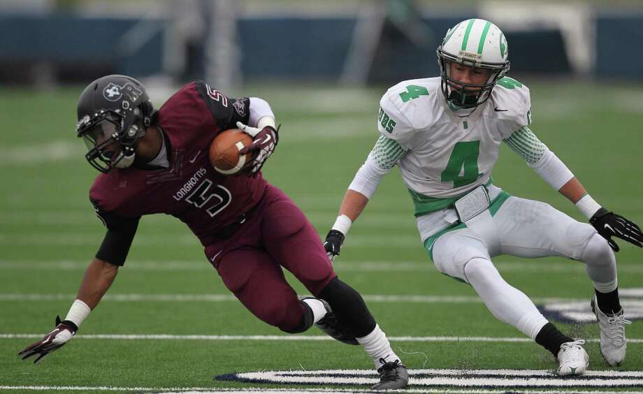 George Ranch's Xavian Marks, left, spins away from Brenham's James Homan during the first half of a high school football playoff game, Saturday, December 7, 2013, at Tully Stadium in Houston. Photo: Eric Christian Smith, For The Chronicle