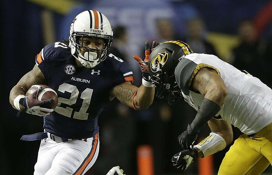 Auburn's Tre Mason (21) tries to evade Missouri's Randy Ponder in his triumphant four-score effort. Photo: Dave Martin, Associated Press