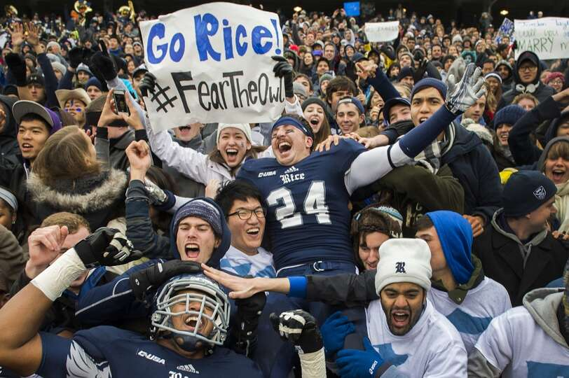 Rice safety Paul Porras (24) and offensive linesman Brandon Dawkins celebrate with fans after the Ow