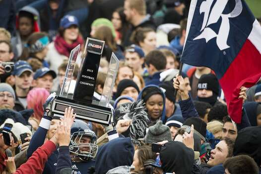 Rice fans storms the field and surround tight end Robby Wells III as he holds up the championship trophy. Photo: Smiley N. Pool, Houston Chronicle
