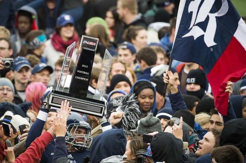 Rice fans storms the field and surround tight end Robby Wells III as he holds up the championship tr