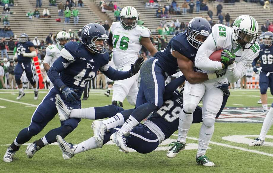 Marshall tight end Gator Hoskins (26) is brought down by Rice cornerback Bryce Callahan (29), linebacker Michael Kutzler (42) and safety Gabe Baker (40). Photo: Smiley N. Pool, Houston Chronicle