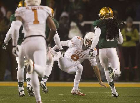 Texas quarterback Case McCoy, middle, falls as he tries to tackle Baylor cornerback K.J. Morton, right, who intercepted McCoy's pass and returned it for a touchdown. Photo: Jay Janner, McClatchy-Tribune News Service